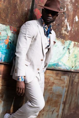 Come indossare: abito a tre pezzi di lino beige, camicia a maniche lunghe a fiori blu, sneakers basse bianche, borsalino di lana marrone