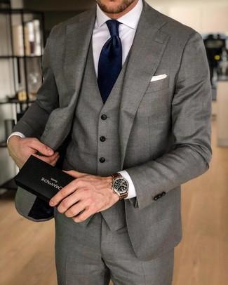 Come indossare e abbinare: abito a tre pezzi grigio, camicia elegante bianca, cravatta di seta blu scuro, fazzoletto da taschino bianco