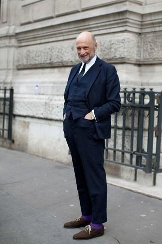 Moda uomo anni 60: Indossa un abito a tre pezzi blu scuro con una camicia elegante bianca per un look elegante e alla moda. Per un look più rilassato, scegli un paio di scarpe brogue in pelle scamosciata marrone scuro.