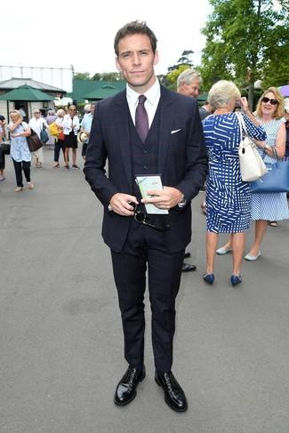 Come indossare e abbinare: abito a tre pezzi a quadri blu scuro, camicia elegante bianca, scarpe derby in pelle nere, cravatta stampata melanzana scuro