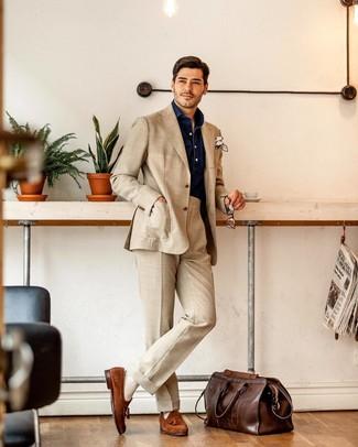 Come indossare e abbinare: abito beige, camicia a maniche lunghe in chambray blu scuro, mocassini con nappine in pelle scamosciata terracotta, borsone in pelle marrone scuro
