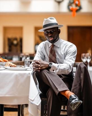 Come indossare e abbinare: abito marrone, camicia a maniche lunghe a righe verticali bianca, scarpe derby in pelle nere, borsalino di lana bianco