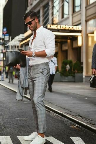 Come indossare e abbinare: abito scozzese grigio, camicia a maniche lunghe bianca, sneakers basse bianche, pochette in pelle nera