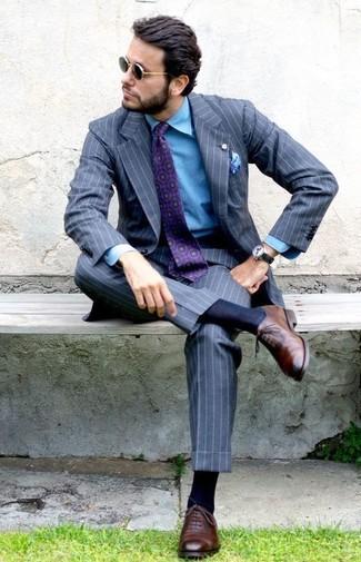 Come indossare e abbinare: abito a righe verticali grigio, camicia di jeans blu, scarpe oxford in pelle marroni, cravatta stampata viola melanzana