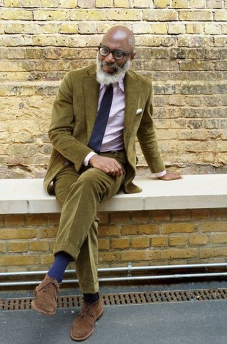Come indossare e abbinare: abito di velluto a coste verde oliva, camicia elegante rosa, chukka in pelle scamosciata marroni, cravatta geometrica blu scuro
