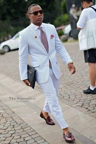 Come indossare e abbinare: abito di seersucker azzurro, camicia elegante bianca, mocassini con nappine in pelle bordeaux, pochette in pelle nera