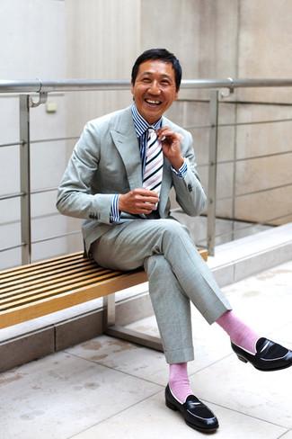 Come indossare e abbinare: abito grigio, camicia elegante a righe verticali bianca e blu scuro, mocassini eleganti in pelle neri, cravatta a righe verticali bianca e nera