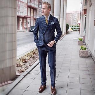 Come indossare e abbinare: abito a righe verticali blu scuro, camicia elegante bianca, scarpe brogue in pelle marroni, cravatta stampata gialla