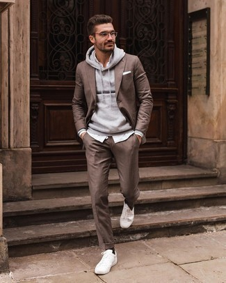 Trend da uomo 2020: Coniuga un abito marrone con una felpa con cappuccio grigia per un look davvero alla moda. Vuoi osare? Completa il tuo look con un paio di sneakers basse di tela bianche.