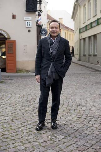 Moda uomo anni 50: Potresti indossare un abito di lana a quadri grigio scuro e una camicia elegante bianca per un look elegante e alla moda. Opta per un paio di scarpe derby in pelle nere per avere un aspetto più rilassato.
