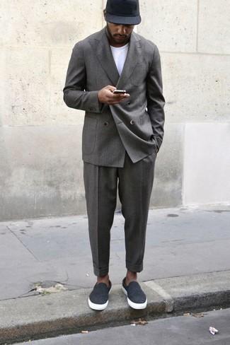 Trend da uomo 2020 in estate 2020: Scegli un abito grigio e una t-shirt girocollo bianca per essere elegante ma non troppo formale. Non vuoi calcare troppo la mano con le scarpe? Prova con un paio di sneakers senza lacci di tela grigio scuro per la giornata. Un look stupendo per essere più cool e trendy anche in estate.