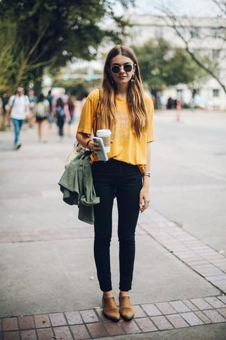 Come indossare e abbinare: anorak verde oliva, t-shirt girocollo stampata senape, jeans aderenti neri, stivali chelsea in pelle marrone chiaro