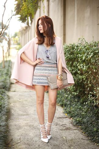 Come indossare e abbinare: blazer a mantella rosa, t-shirt con scollo a v grigia, minigonna geometrica grigia, sandali con tacco in pelle bianchi