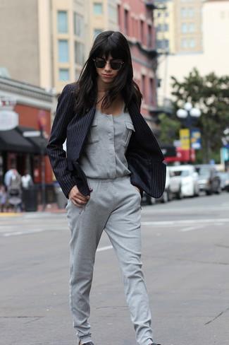 Come indossare: blazer a righe verticali nero, tuta grigia, sneakers senza lacci in pelle nere