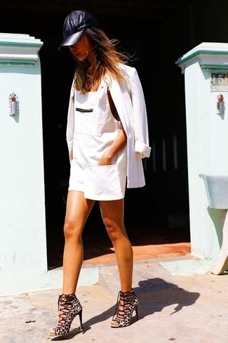 Come indossare e abbinare: blazer bianco, salopette corta di jeans bianca, sandali con tacco in pelle scamosciata leopardati marrone chiaro, berretto da baseball in pelle nero