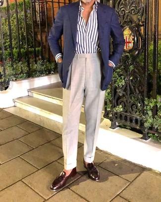 Come indossare e abbinare: blazer blu scuro, camicia a maniche lunghe a righe verticali bianca e blu scuro, pantaloni eleganti beige, mocassini con nappine in pelle marrone scuro