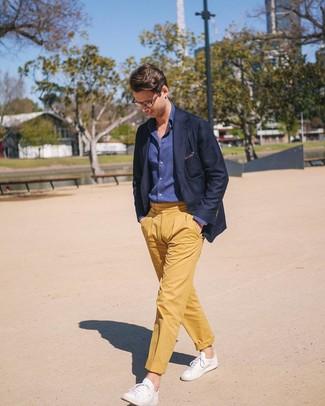 Come indossare e abbinare: blazer blu scuro, camicia a maniche lunghe in chambray blu scuro, chino gialli, sneakers basse in pelle bianche
