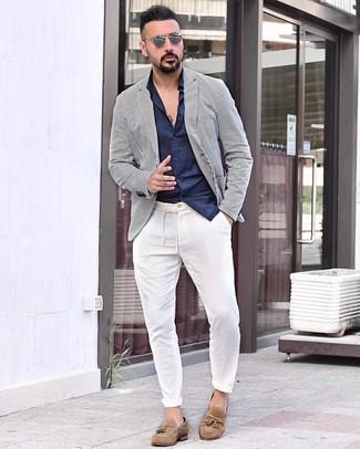 Come indossare e abbinare: blazer a righe verticali bianco e blu scuro, camicia a maniche lunghe blu scuro, chino bianchi, mocassini con nappine in pelle scamosciata marrone chiaro