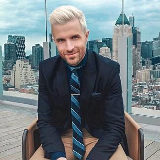 Come indossare e abbinare: blazer di lana blu scuro, camicia elegante blu scuro, chino marroni, cravatta a righe verticali foglia di tè