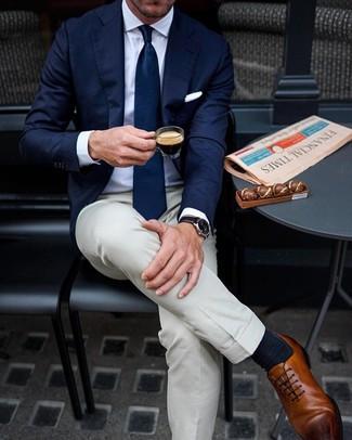 Come indossare e abbinare pantaloni eleganti beige: Coniuga un blazer blu scuro con pantaloni eleganti beige per un look elegante e alla moda. Scarpe oxford in pelle marroni sono una buona scelta per completare il look.
