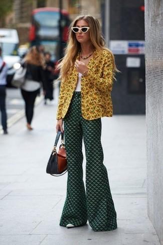 Come indossare e abbinare: blazer a fiori giallo, canotta bianca, pantaloni a campana a fiori verde scuro, décolleté in pelle bianchi