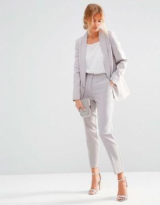 Come indossare: blazer grigio, canotta di seta bianca, pantaloni eleganti grigi, sandali con tacco in pelle argento