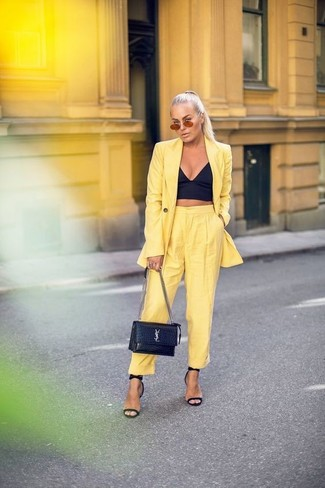 Come indossare: blazer giallo, corsetto nero, pantaloni stretti in fondo gialli, sandali con tacco in pelle neri