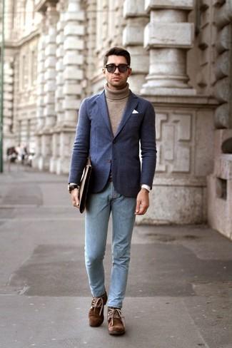 Come indossare e abbinare: blazer di lana blu scuro, dolcevita marrone, jeans aderenti azzurri, chukka in pelle scamosciata marroni
