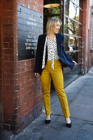 Come indossare: blazer doppiopetto blu scuro, blusa abbottonata a pois bianca e nera, pantaloni skinny senapi, décolleté in pelle scamosciata neri
