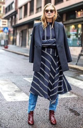Come indossare e abbinare: blazer doppiopetto blu scuro, vestito longuette a righe orizzontali blu scuro e bianco, jeans azzurri, stivaletti in pelle bordeaux