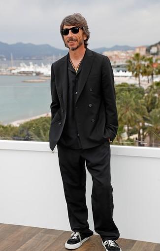 Come indossare e abbinare: blazer doppiopetto nero, camicia a maniche lunghe nera, pantaloni eleganti neri, sneakers basse di tela nere e bianche