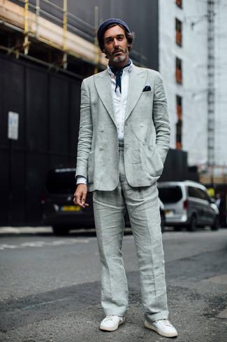 Come indossare e abbinare: blazer doppiopetto di lino grigio, camicia a maniche lunghe bianca, pantaloni eleganti di lino grigi, sneakers basse in pelle bianche