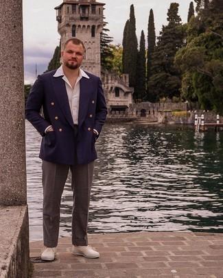 Trend da uomo 2021: Combina un blazer doppiopetto blu scuro con pantaloni eleganti marrone scuro per essere sofisticato e di classe. Scegli un paio di sneakers basse di tela beige per avere un aspetto più rilassato.
