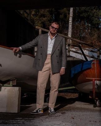 Trend da uomo 2021: Scegli un blazer doppiopetto di lana scozzese grigio scuro e pantaloni eleganti marrone chiaro per essere sofisticato e di classe. Scegli uno stile casual per le calzature con un paio di sneakers alte in pelle bianche e nere.