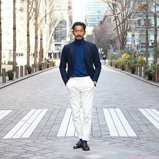 Trend da uomo 2020 in primavera 2021: Opta per un blazer doppiopetto blu scuro e pantaloni eleganti bianchi per un look elegante e alla moda. Per distinguerti dagli altri, scegli un paio di mocassini con nappine in pelle neri. Questo è il look fantastico per la primavera.