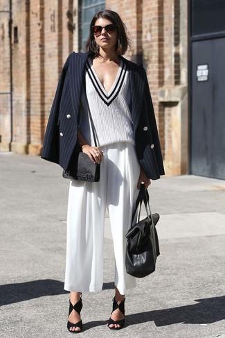 Come indossare: blazer doppiopetto a righe verticali nero, maglione con scollo a v bianco e nero, gonna pantalone bianca, sandali con tacco in pelle scamosciata neri