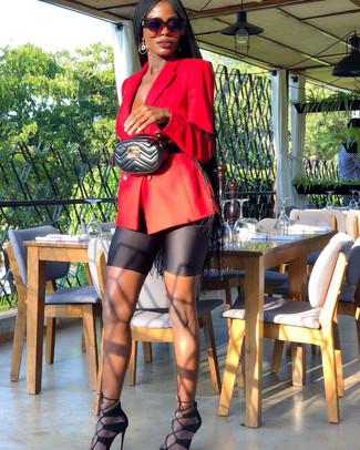 Come indossare: blazer doppiopetto rosso, pantaloncini ciclisti neri, sandali con tacco in pelle scamosciata neri, marsupio in pelle trapuntato nero