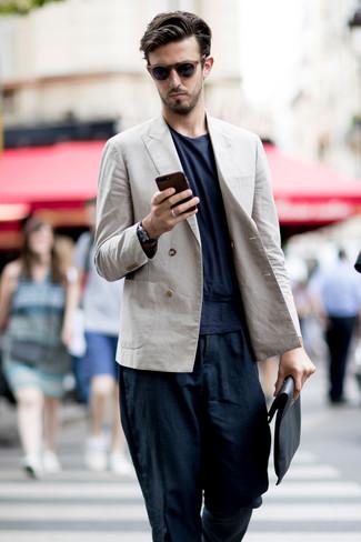 Come indossare e abbinare: blazer doppiopetto di lino beige, t-shirt girocollo blu scuro, chino di lino blu scuro, pochette in pelle nera