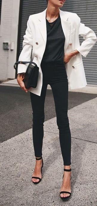 Come indossare: blazer doppiopetto bianco, t-shirt girocollo nera, jeans aderenti neri, sandali con tacco in pelle scamosciata neri