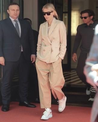 Moda donna anni 40: Scegli un outfit composto da un blazer doppiopetto beige e pantaloni larghi marrone chiaro per un drink dopo il lavoro. Per distinguerti dagli altri, calza un paio di sneakers basse in pelle bianche.