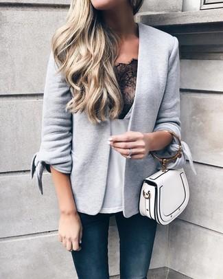 Come indossare e abbinare: blazer lavorato a maglia grigio, canotta di pizzo bianca e nera, jeans aderenti blu scuro, borsa a mano in pelle bianca