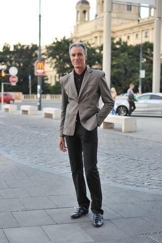 Moda uomo anni 50: Indossa un blazer grigio con chino neri, perfetto per il lavoro. Opta per un paio di scarpe double monk in pelle nere per mettere in mostra il tuo gusto per le scarpe di alta moda.