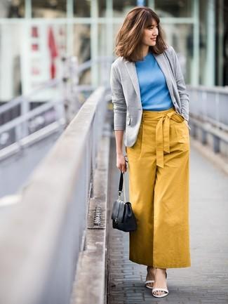 Come indossare: blazer lavorato a maglia grigio, maglione a maniche corte blu, pantaloni larghi senapi, sandali con tacco in pelle bianchi