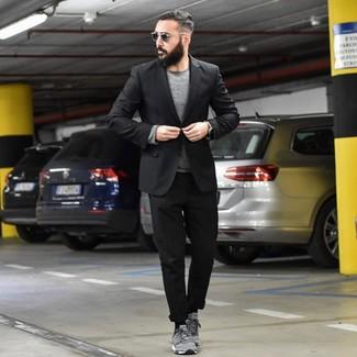 Come indossare e abbinare: blazer nero, maglione girocollo grigio, chino neri, sneakers basse in pelle scamosciata grigie