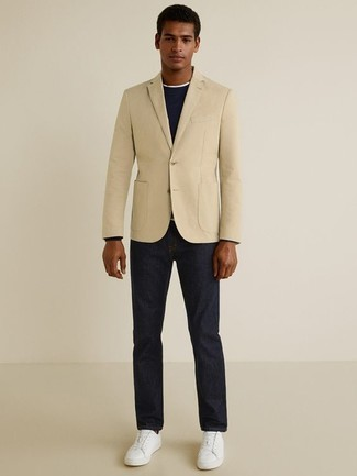 Trend da uomo 2020: Mostra il tuo stile in un blazer beige con jeans blu scuro per un look davvero alla moda. Non vuoi calcare troppo la mano con le scarpe? Prova con un paio di sneakers basse in pelle bianche per la giornata.