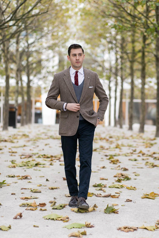 Come indossare e abbinare: blazer di tweed a spina di pesce marrone, maglione senza maniche grigio scuro, camicia elegante bianca, chino blu scuro