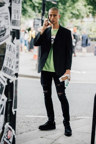 Come indossare e abbinare: blazer nero, t-shirt girocollo stampata verde, jeans aderenti strappati neri, scarpe derby in pelle pesanti nere