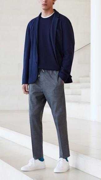 Trend da uomo 2020: Mostra il tuo stile in un blazer blu scuro con chino grigio scuro per un abbigliamento elegante ma casual. Scegli un paio di sneakers basse di tela bianche per un tocco più rilassato.
