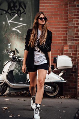 Come indossare: blazer nero, t-shirt girocollo stampata bianca e nera, pantaloncini ciclisti neri, stivali piatti stringati in pelle bianchi