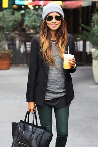 Indossa un blazer nero con jeans aderenti verde scuro per un pranzo domenicale con gli amici.
